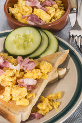 scrambled eggs with fried bacon, toasted bread and sliced cucumber