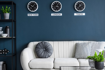 Cushions placed on light grey couch in dark living room interior with three clocks and fresh green plants