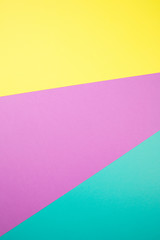 multi-color paper geometric background made of cardboard sheets. yellow, turquoise, purple rays