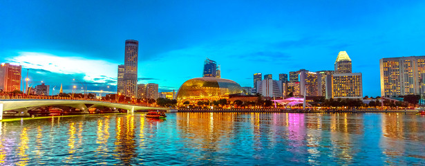 Skyline of Singapore in marina bay with cruise sails in the harbor at blue hour. Tourist boat on foreground. Night scene waterfront in Singapore bay.