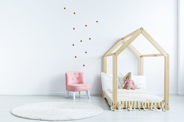 Pink chair against white wall with stickers in simple kid's bedroom interior with wooden bed. Real photo