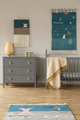 Decor on the wall above grey cabinet and child's bed with blanket in bedroom interior. Real photo
