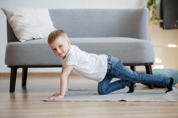 Photo of boy in white T-shirt playing on floor near sofa