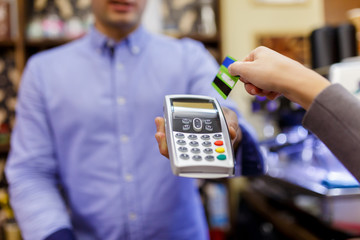 Photo of seller with terminal in hands and buyer with bank card.