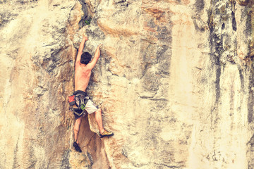 A young male climber climbs on a rock without a safety rope