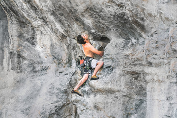Young male climber climbs on a rock without a safety rope