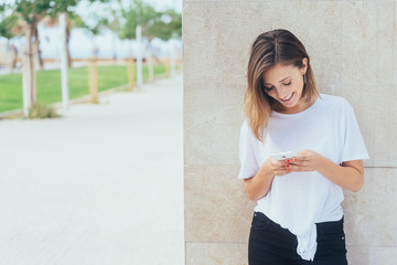Young woman standing texting a message on a mobile