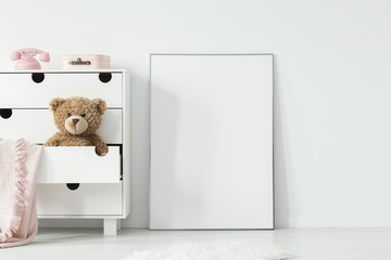 Plush toy and pink blanket in cabinet next to empty white poster in baby's room interior. Real photo. Paste your photo here