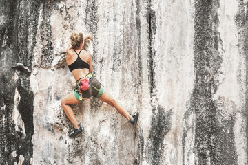 Young female rock climber climbing the cliff without safety equipment, copy space. Toned