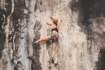 Young female rock climber climbing a cliff without insurance. Toned