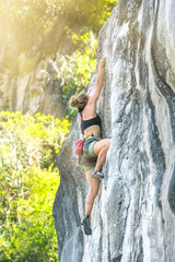 Young woman climbing a rock on a sunny summer day
