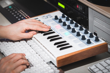 professional musician hands working on midi keyboard and computer in recording studio