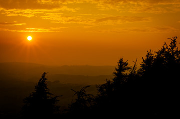 A deep orange sunset silhouettes the trees and fields at the Roaches in the Peak District National park.