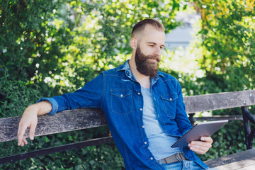 Man sitting relaxing reading a tablet