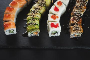 Set of different sushi rolls on black background