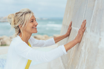Happy blond woman leaning her hands on a wall