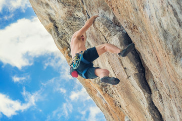 Young male climber climbing a rock wall without safety rope
