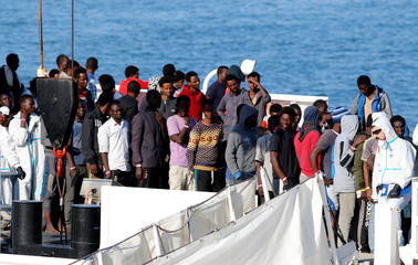 "Migrants wait to disembark Italian Coast Guard's vessel ""Diciotti"" as they arrive at the Catania harbour"