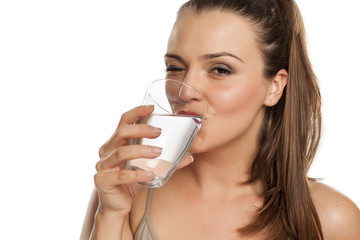 happy woman drinks water from a glass on white background and winks