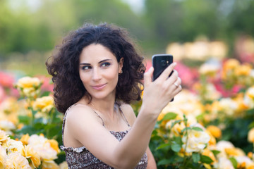 A portrait of Caucasian woman with dark curly hair taking selfie near yellow rose bushes in a rose garden
