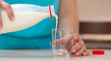 Hand of unidentified young woman pouring milk into glass standing on the kitchen table. Concept of healthy eating