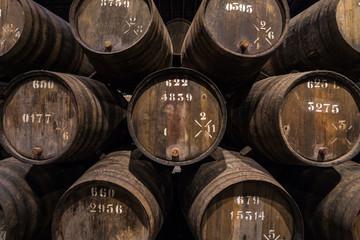 Row of wooden porto wine barrels in wine cellar Porto, Portugal. Fototapete