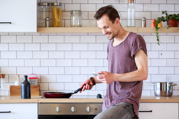 Portrait of man with frying pan and phone in hands in kitchen