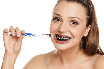 young woman brushing her teeth with black toothpaste of activated charcoal on white background