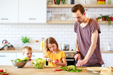 Photo of young father with daughter cooking vegetables