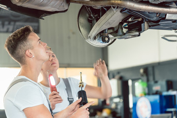 Side view of a skilled auto mechanic replacing the shock absorbers of a lifted car, while working together with his colleague in a modern automobile repair shop