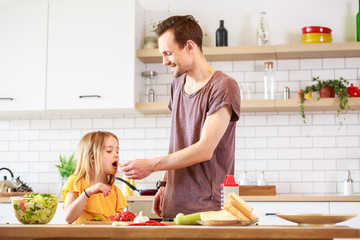Image of young father with daughter cooking lunch