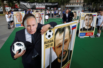 A Reporter Without Borders (RSF) activist, wearing a mask depicting Russian President Vladimir Putin, stands next to a giant portrait of journalist Alexei Kungurov on Place de la Republique in Paris