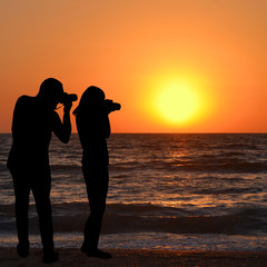 Silhouette of man and woman photographers take a sunrise picture