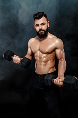 athletic muscular man doing exercises with dumbbells.
