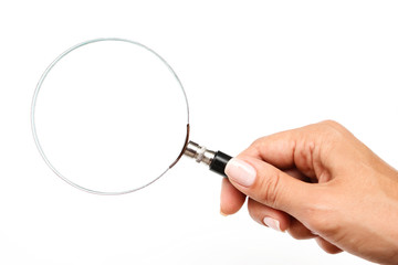 Female hand with a magnifying glass on a white background