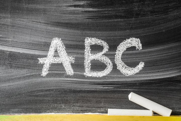 Drawn letters by chalk. Teaching abc alphabet letters for little kids on the blackboard. Education concept.