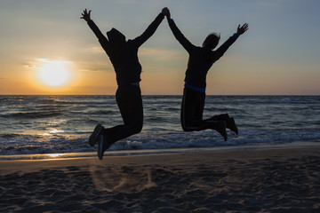 Two happy girls having fun and standing with raised arms on background of sunset sea.