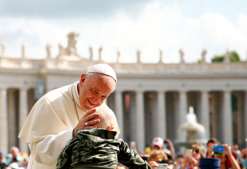 Pope Francis blesses a child as he arrives to lead the Wednesday general audience in Saint Peter's square at the Vatican