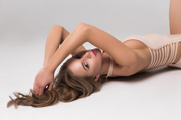 Be in style! Gorgeous smart young woman wearing beige lingerie and touching her hair, while being on the floor and posing for photo.