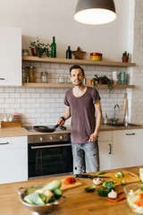 Image of man with frying pan in hands in kitchen