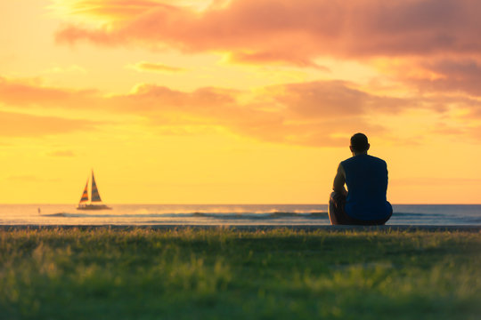 Man relaxing by the sea watching the colourful sunset and sail boats go by.