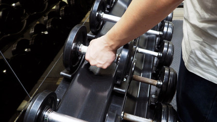 Dumbbells row with arm equipment in fitness.