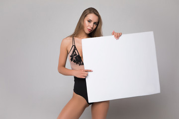 Elegance is a glowing inner peace! Gorgeous young woman wearing sexy lingerie posing for the picture with empty board on the isolated grey background.
