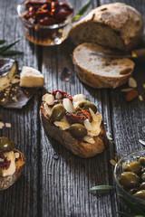 Tapas de Pain Grillé à la Tomme de Provence, Olive verte, Tomate Séchée et Amandes