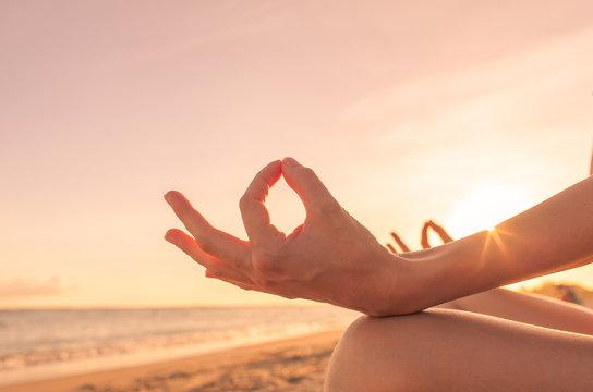 Closeup of hand meditating against sunset sky. .