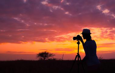 Female photographer capturing a beautiful sunset.