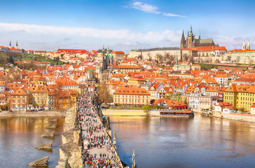 View of Charles Bridge, Prague Castle and Vltava river in Prague, Czech Republic from above. Nice sunny summer day with blue sky and clouds. Famous landmarks in Europe.