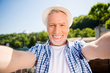 Self portrait of cheerful positive man in straw hat with beaming toothy smile shooting selfie on front camera over blurred street background