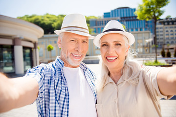 Portrait of stylish cheerful senior couple in straw hats shooting selfie on front camera over street background. Rest relax walk leisure weekend concept