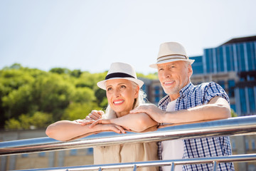 Portrait of attractive cheerful couple in straw hats casual outfit enjoying beautiful view lean on balcony railing looking away spending time together. Vacation weekend holiday concept